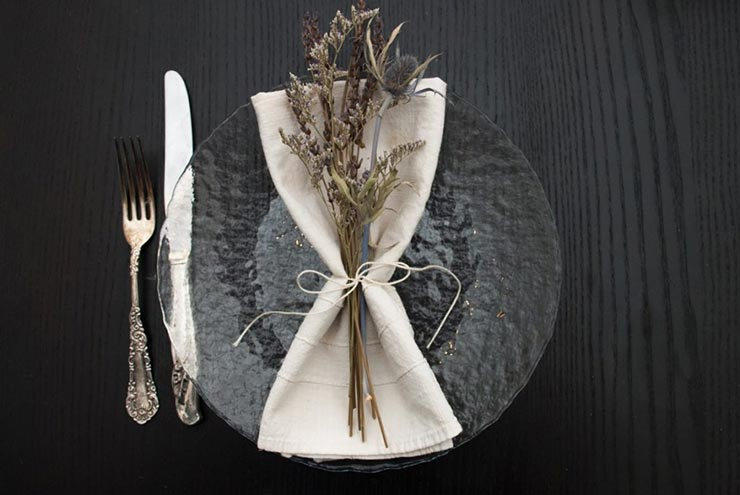 A clear plate on a black table with a napkin and dry thistle and lavender flowers tied to it with string, beside an antique knife and fork.