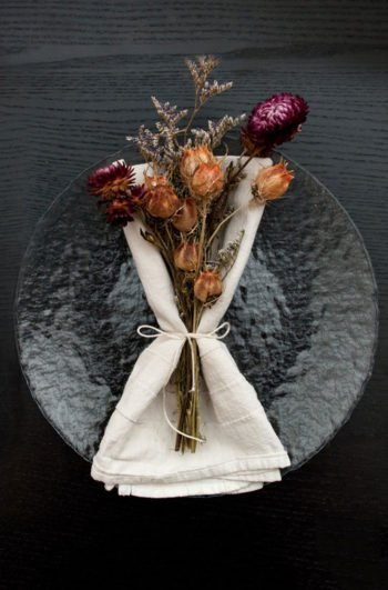 A clear plate on a black table with a napkin and bright dry flowers tied to it with string.