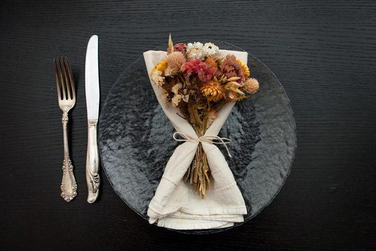 A clear plate on a black table with a napkin and bright and fluffy dry flowers tied to it with string, beside an antique knife and fork.