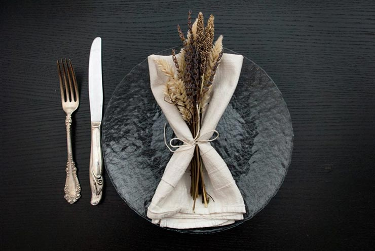A clear plate on a black table with a napkin and dry, purple and white flowers tied to it with string, beside an antique knife and fork.