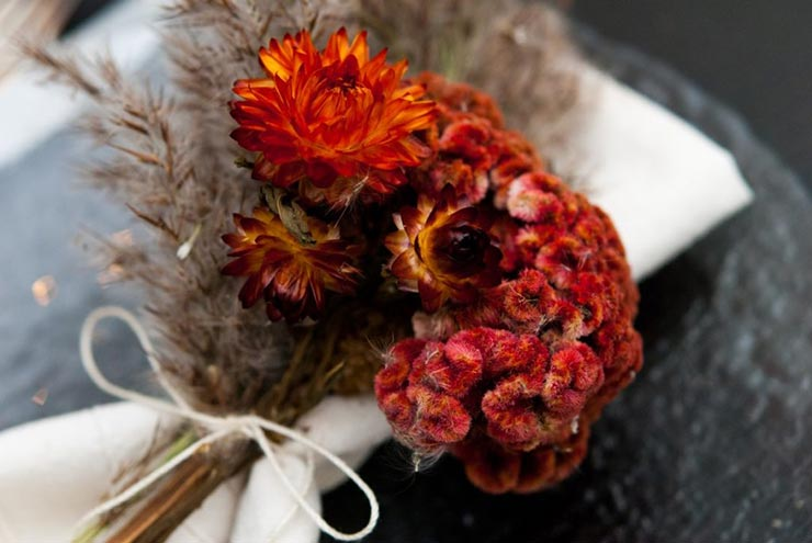 A closeup of bright red and fluffy dry flowers tied to a napkin.