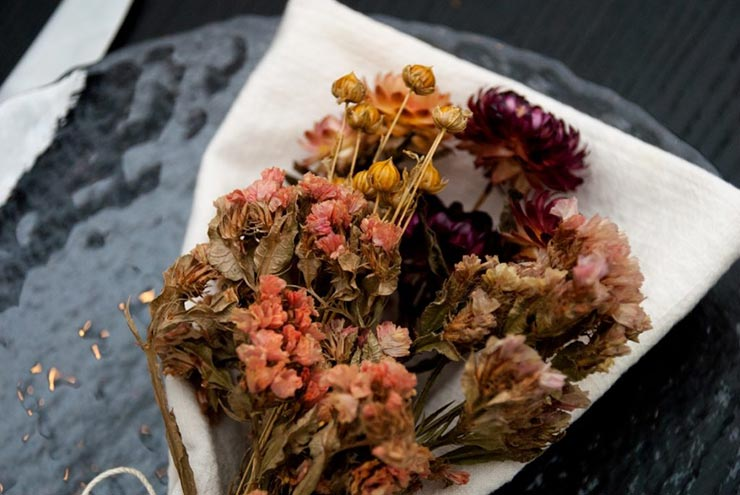 A closeup of bright, dry flowers tied to a napkin on a plate.