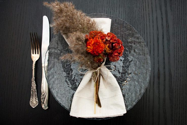 A clear plate on a table with a napkin and bright, fluffy dry flowers tied to it with string, next to a knife and fork.