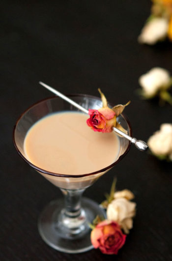 A small cocktail, garnished with a pink spray rose, pierced with a cocktail pin on a black table, surrounded by a few scattered roses.