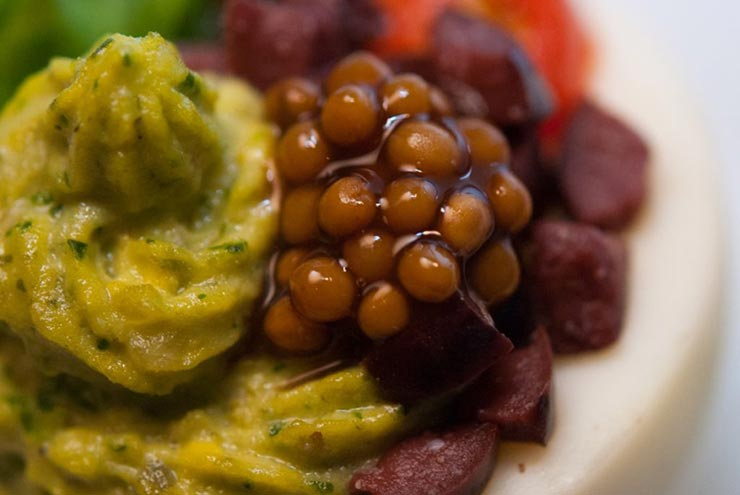 A closeup of a green deviled egg, garnished with mustard caviar, diced olives, a tiny sliced tomato and a small leaf of basil.