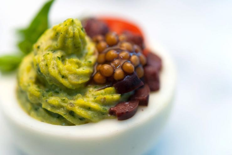 A green deviled egg, garnished with mustard caviar, diced olives, a tiny sliced tomato and a small leaf of basil.