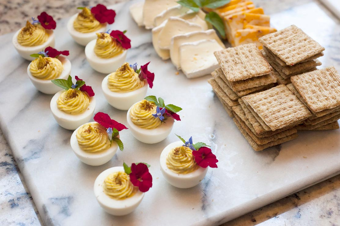 10 deviled eggs, garnished with flowers on a marble cheese board next to crackers and sliced cheese.