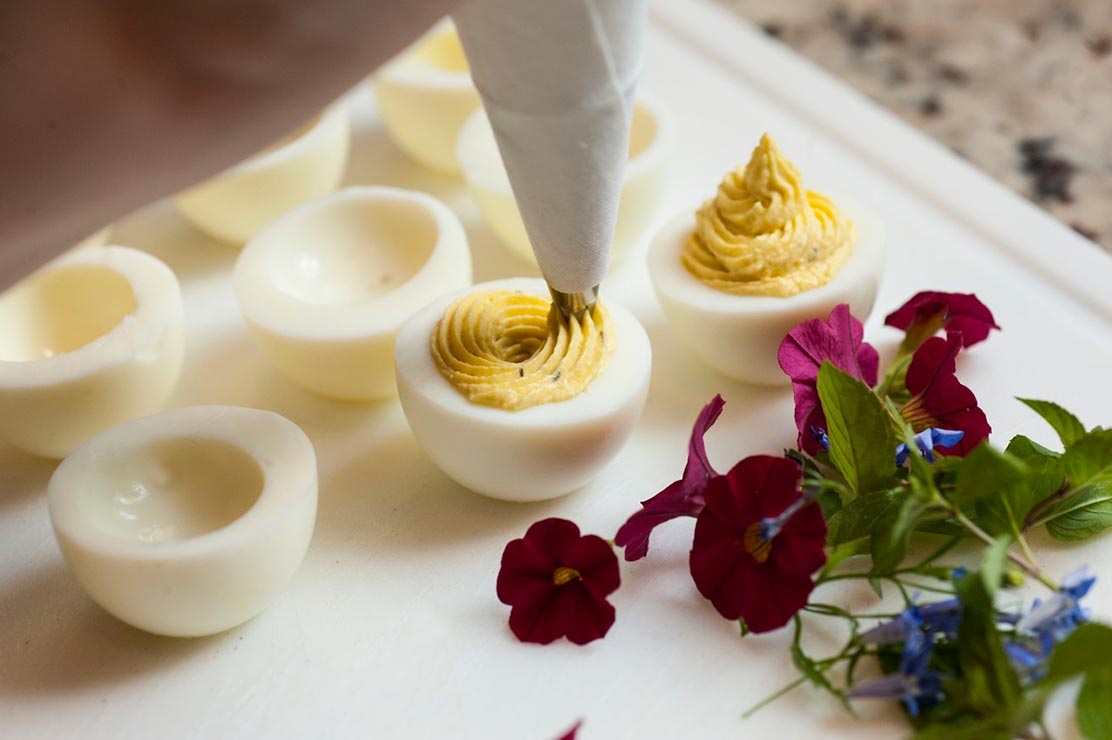 A pastry piping bag filling 2 deviled eggs on a cutting board next to garnish flowers.