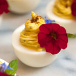 A deviled egg on a marble plate garnished with a flower beside 3 others out of frame.