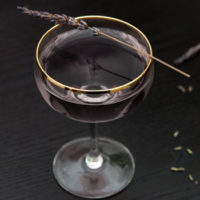 A cocktail on a dark table, garnished with a sprig of lavender, with a few scattered lavender flowers on the table.
