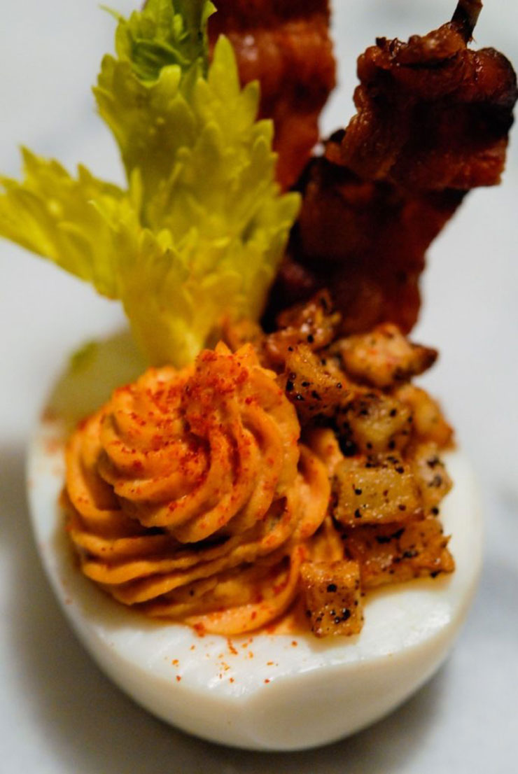 A closeup of a deviled egg with bacon, celery, and tiny hash browns on a marble table.