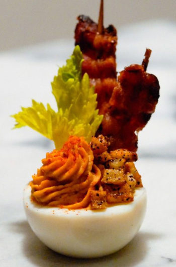 A deviled egg with bacon, celery, and tiny hash browns on a marble table.