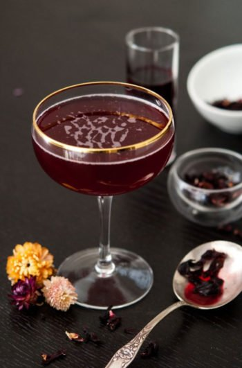 A deep red cocktail in a gold-rimmed glass, surrounded by small flowers, a spoon with wet hibiscus, and other smaller bowls and cps containing flowers or hibiscus liqueur on a black table.
