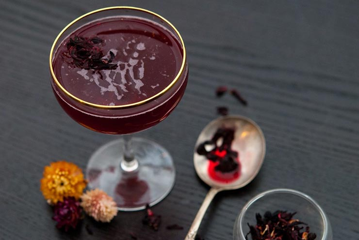 A deep red cocktail in a gold-rimmed glass, surrounded by small flowers, a spoon with wet hibiscus, and a small bowl containing hibiscus flowers on a black table.
