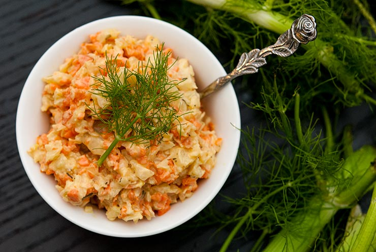 A bowl of fennel & carrot coleslaw in a small white bowl, garnished with a fennel frond next to larger fennel fronds on a black table.