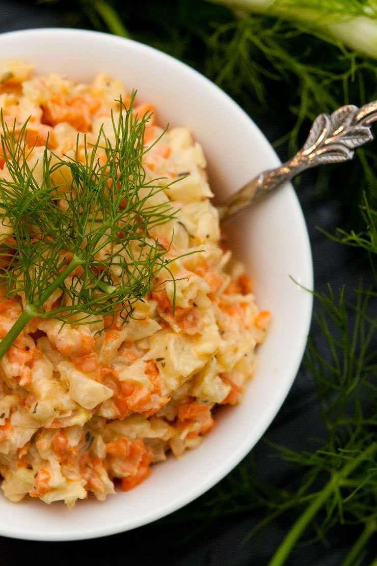 A bowl of fennel & carrot coleslaw in a small white bowl, garnished with a fennel frond next to larger fronds on a table.