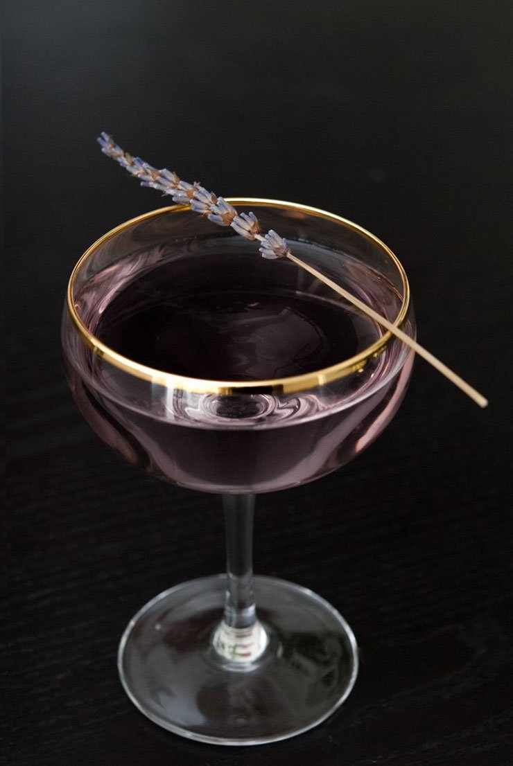 A purple cocktail on a black table, garnished with a sprig of lavender.