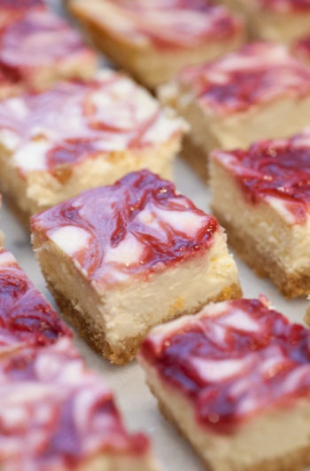 Raspberry marbled lemon cheesecake bars on a marble table.