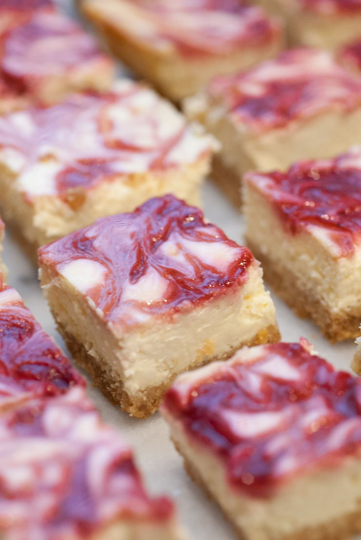 Raspberry marbled lemon cheesecake bars on a marble table.
