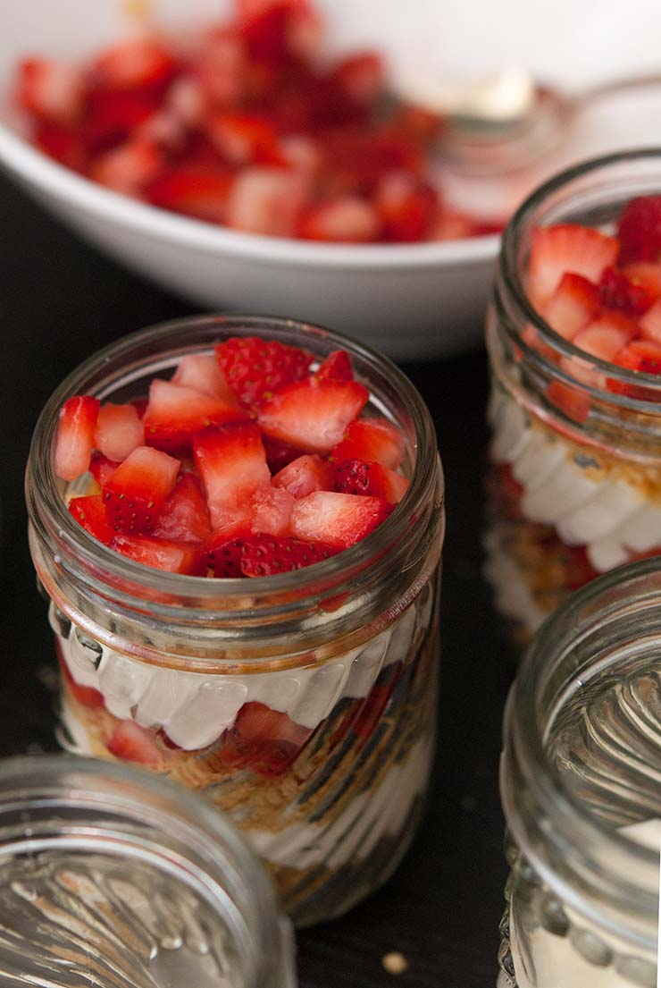 A closeup of a jar of lemon mousse with strawberries on top, surrounded by other full jars and a bowl of chopped strawberries in the background.