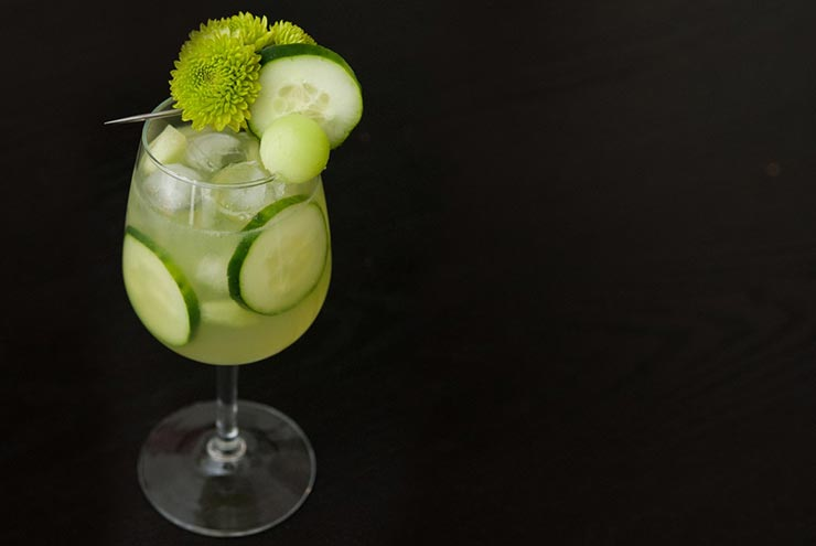 A cocktail in a glass with ice, cucumber slices and garnished with green flowers, cucumber and a honeydew ball.