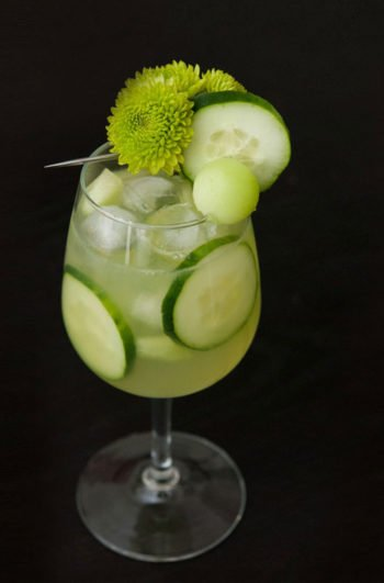 A green cocktail on a black table, garnished with aren flowers, cucumber and a ball of honeydew with cucumbers in the glass.