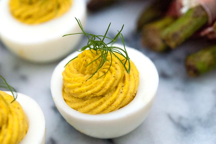3 Deviled eggs on a marble slate, garnished with a sprig of fresh dill.
