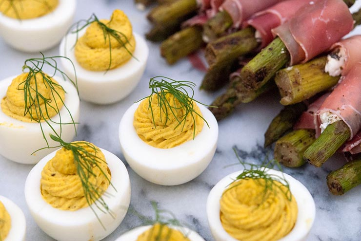 7 deviled eggs on a marble slate, garnished with a sprig of fresh dill, next to prosciutto-wrapped asparagus.