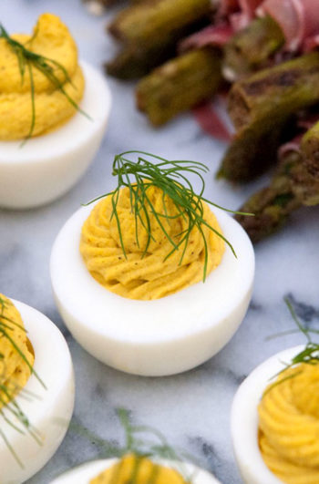 3 deviled eggs on a marble slate, garnished with a sprig of fresh dill, next to prosciutto-wrapped asparagus.