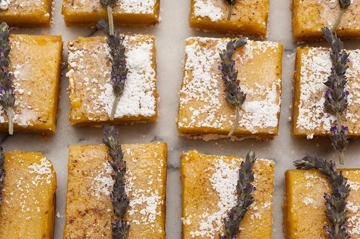Lavender lemon bars, topped with fresh lavender on a white marble tray.