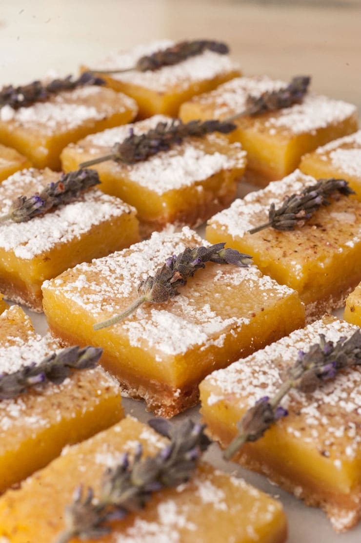 Lavender lemon bars on a white marble table garnished with fresh lavender and powdered sugar.