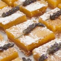 6 lavender lemon bars on a marble plate, topped with sprigs of lavender and sprinkled with powdered sugar.