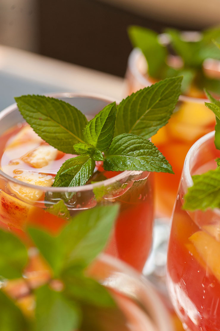 A closeup of a glass of fruit-filled watermelon sangria, garnished with mint, next to a few other full, garnished glasses.