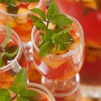 A sangria cocktail garnished with mint, filled with fruit, on a serving tray beside 3 other glasses of sangria.