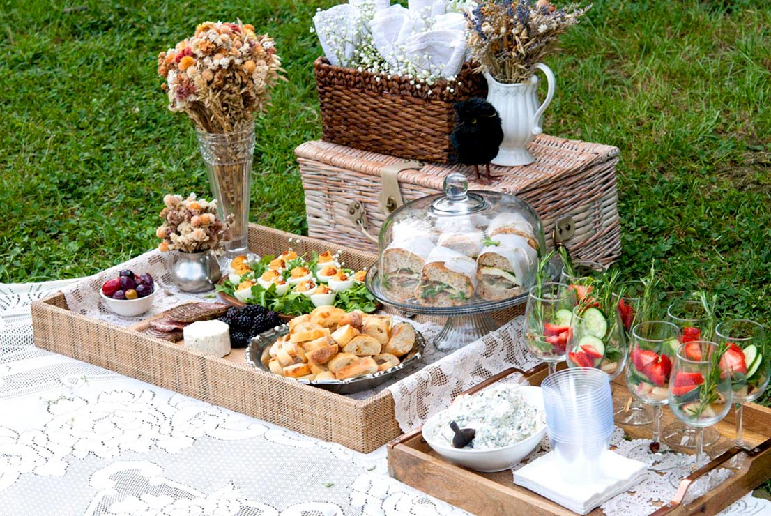 An elaborate picnic spread. Trays of food, flowers, picnic basket and glassware on a lace blanket.