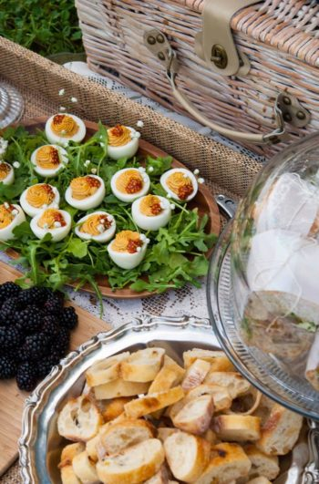 A picnic spread of fresh cut baguette, a plate of deviled eggs and sandwiches on a platter beside a picnic basket.