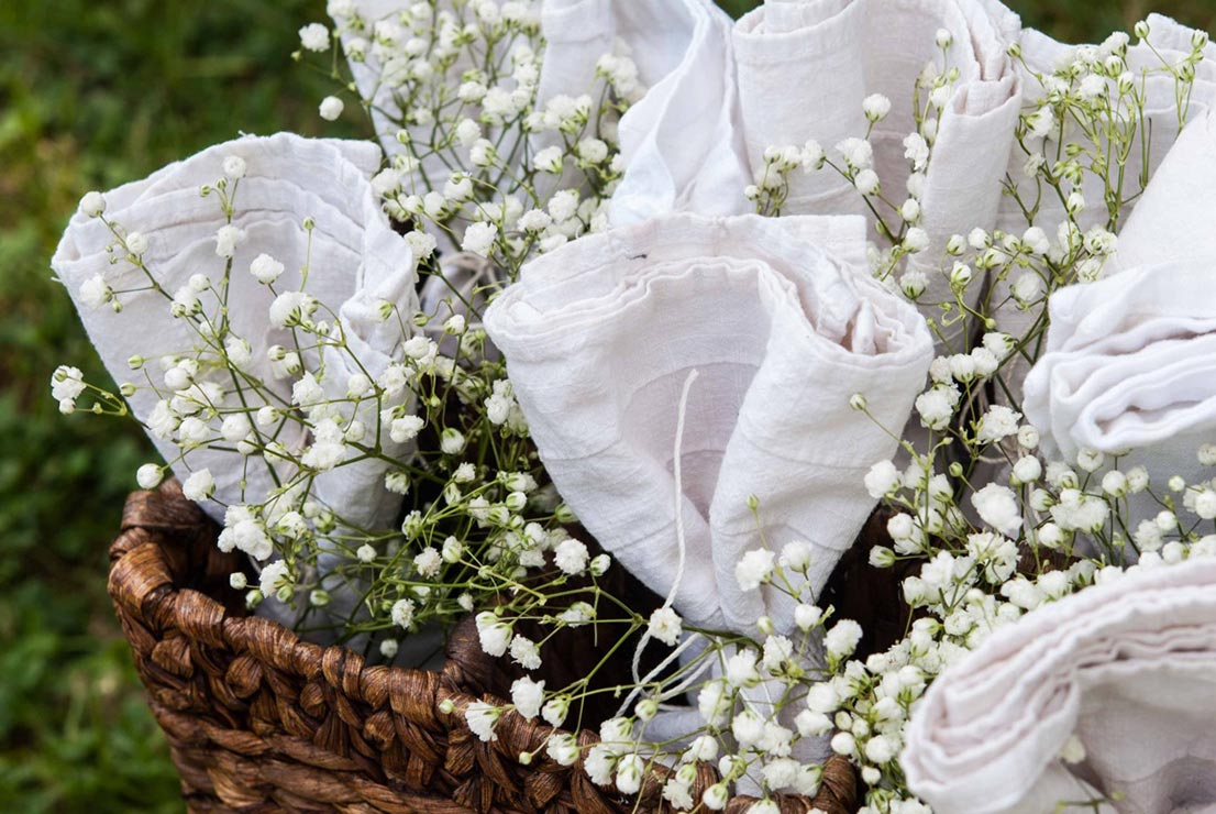 Napkins tied with string in a basket with baby's breath.