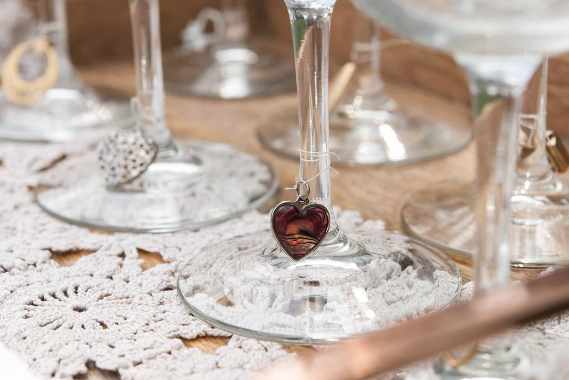 A heart shaped charm tied with thread to the base of a wine glass on top of a doily with 4 other glasses on a wooden tray.