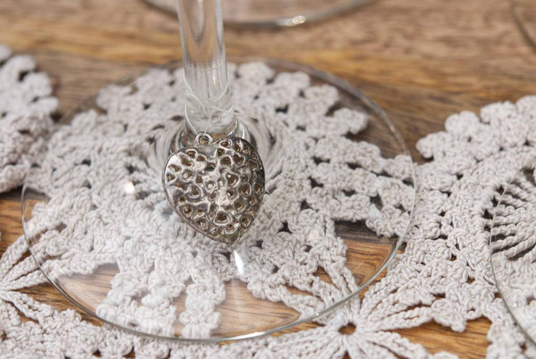A heart shaped charm tied with thread to the base of a wine glass on top of a doily.