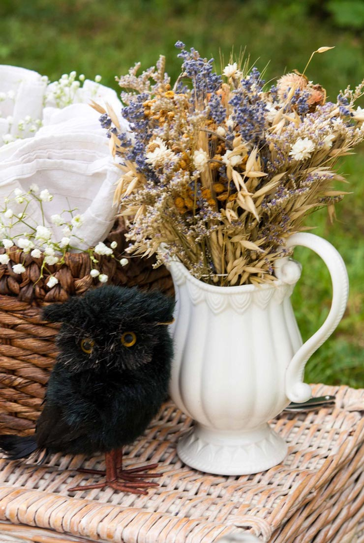 A fake black bird sitting on a picnic basket next to flowers in a white jug, next to a basket full of napkins.