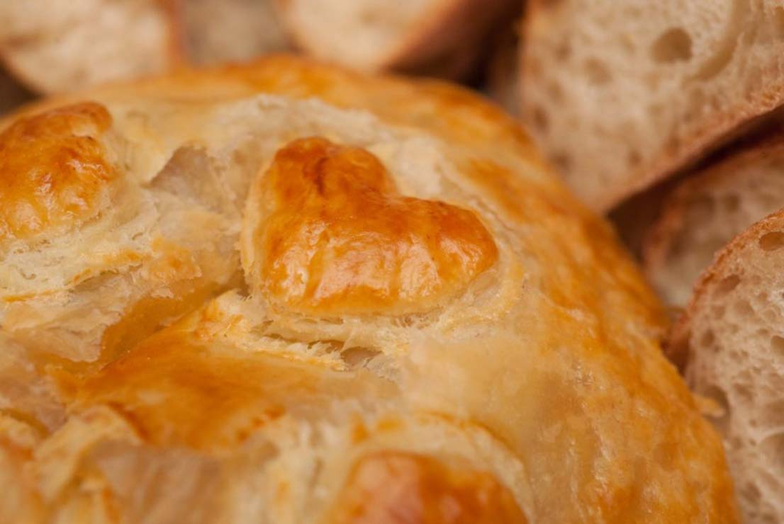 A closeup of a pastry heart on top of a baked gruyere.