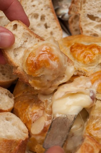 Hands serving holding a cheese knife digging into a baked gruyere surrounded by slides pieces of bread.