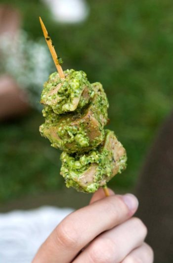 A hand holding a skewer with 3 pieces of chicken, covered in pesto.