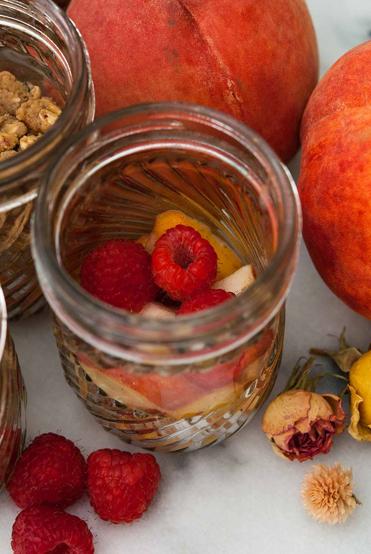 A jar with raspberries and peaches on a marble slate next to 2 large peaches with raspberries and dry flowers sprinkled around the jar.