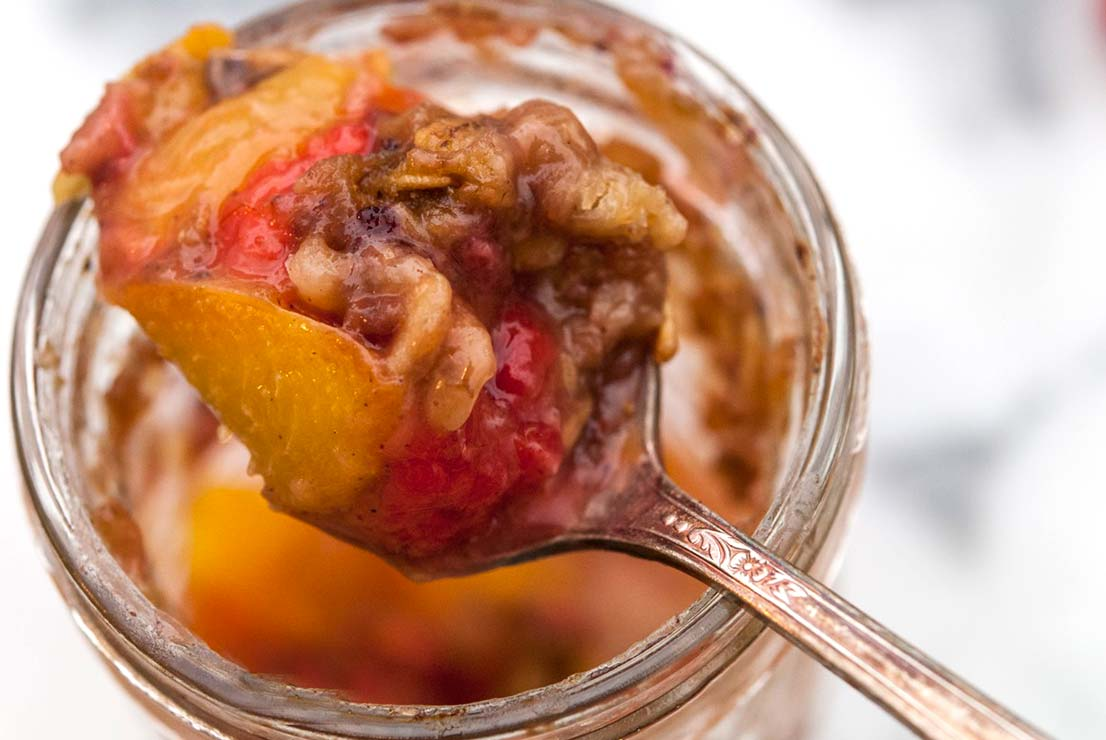 A spoon full of peach & raspberry crisp above a jar on a white marble table.