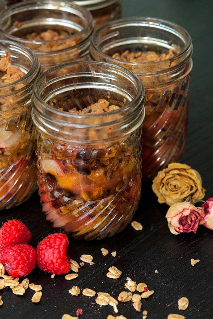4 jars of raspberry & peach crisp surrounded by raspberries, dry flowers and a sprinkle of granola on a black table.