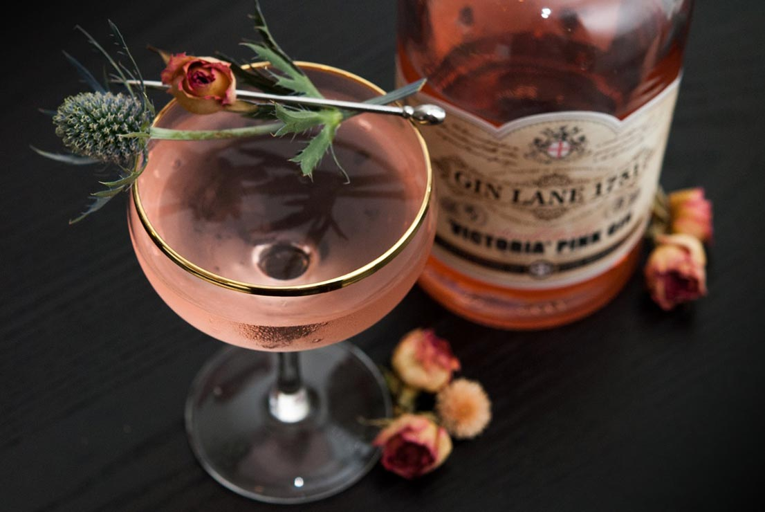 A pink cocktail, garnished with a pink spray rose and a sprig of thistle on a black table, next to a bottle of Gin Lane Pink Gin.