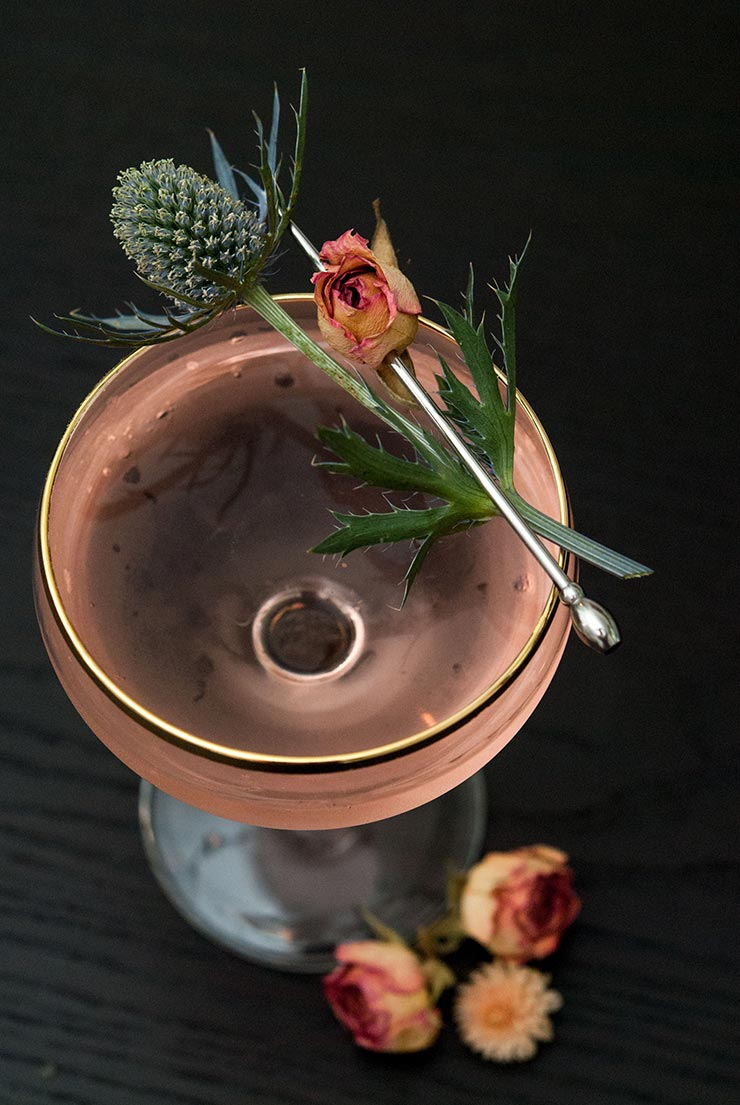 A closeup of a pink cocktail, garnished with a pink spray rose and a sprig of thistle on a black table.