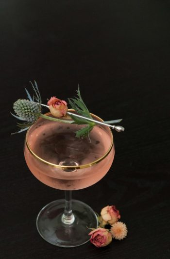 A pink cocktail, garnished with a pink spray rose and a sprig of thistle on a black table.