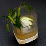 A tumbler glass cocktail with a large ice cube and 3 slices of green apple fanned out on top, garnished with greenery.
